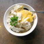 Photo of scalloped potatoes topped with cheese and parsley in a round white bowl
