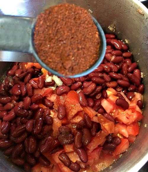 Photo of chili powder in a measuring spoon being added to a large pot of chili
