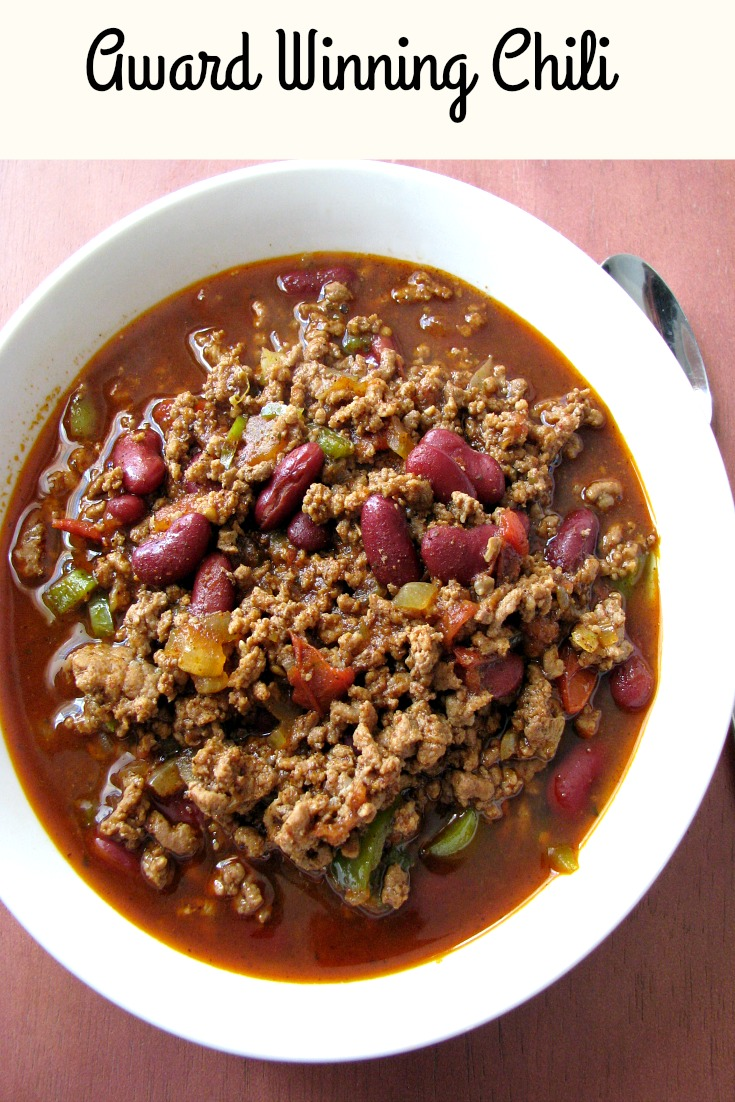 Photo of Award Winning Chili in a white bowl on a wood table with text at the top stating Award Winning Chili