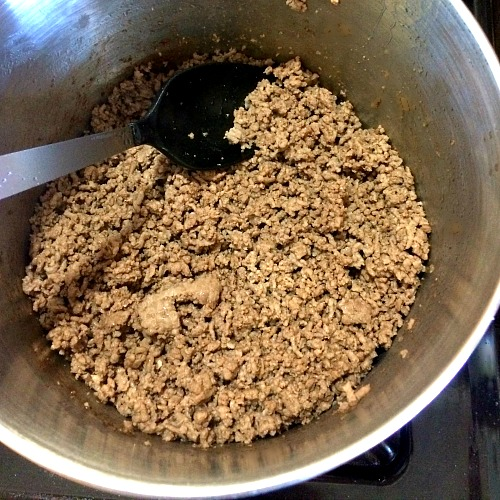 Photo of cooked ground beef in a large pot with a black spoon