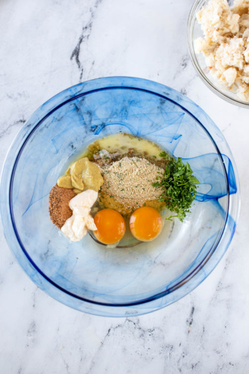 eggs seasonings and breadcrumbs in a clear glass bowl