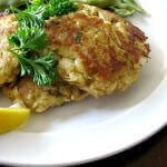 Photo of crab cakes topped with parsley with a lemon slice on the left side