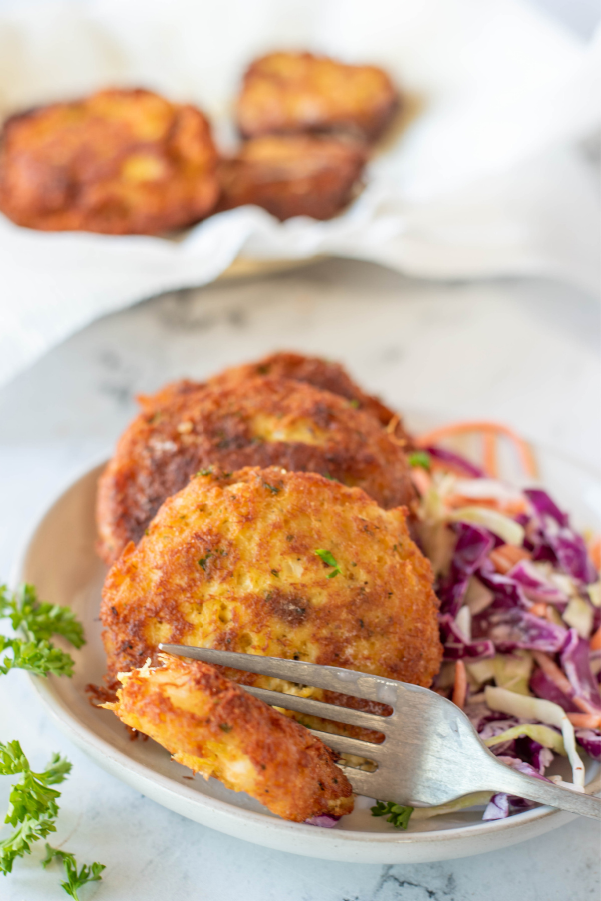 two crab cakes on a plate with a fork cutting in to one crab cake