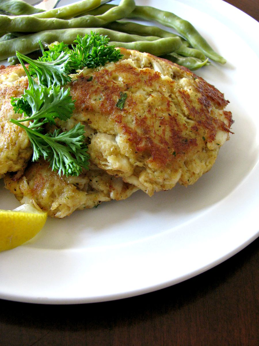 Photo of a plate of crab cakes with green beans in the background