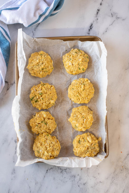 crab mixture shaped into patties on a parchment lined baking sheet