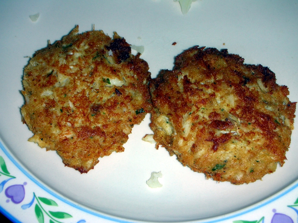 photo of two crab cakes on a bluish white plate