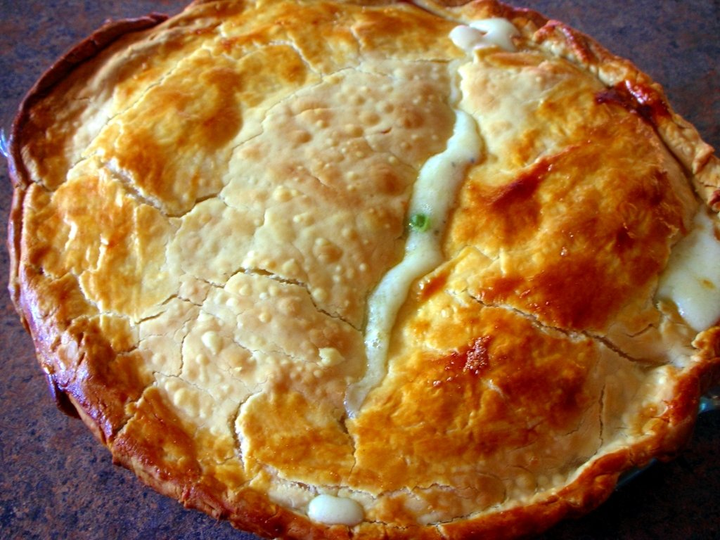 Whole baked Chicken Pot Pie in pie pan on a brown counter top