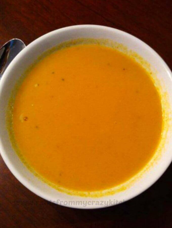 Photo of Pumpkin Soup in a white bowl on a dark wood table