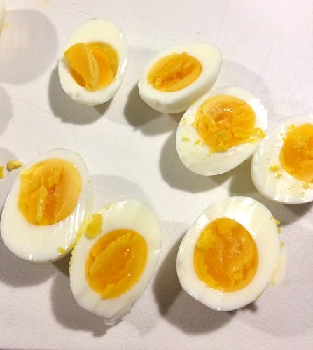 Photo of sliced hard cooked eggs on a white cutting board