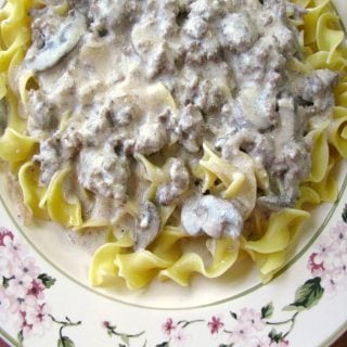 photo of Easy Beef Stroganoff over egg noodles on a white plate with flower trim