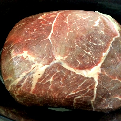 photo of uncooked roast beef in a black slow cooker