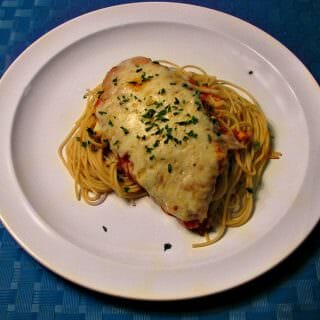 Photo of plated Chicken Parmesan over thin spaghetti on a white plate with a blue place mat