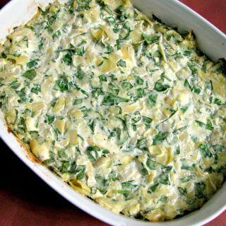 Spinach Artichoke Dip, made with fresh or frozen spinach, canned artichokes, cream cheese, and Gouda cheese, then baked or cooked in the slow cooker.