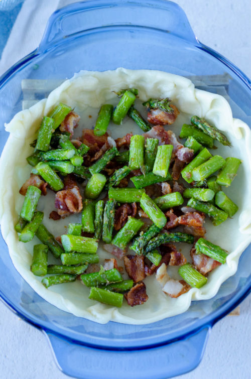 cooked asparagus and bacon in the bottom of a partially baked pie crust