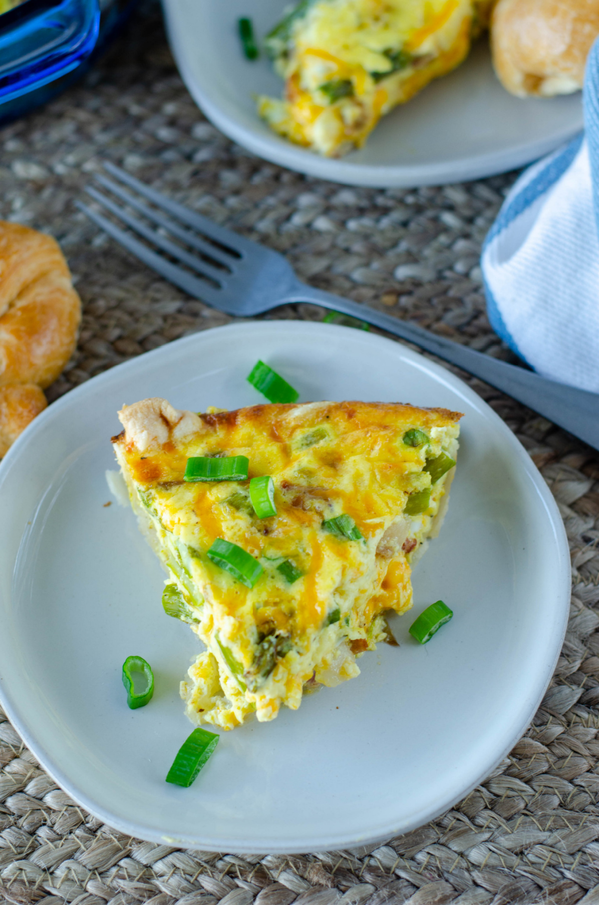 a slice of quiche on a white plate garnished with sliced scallions