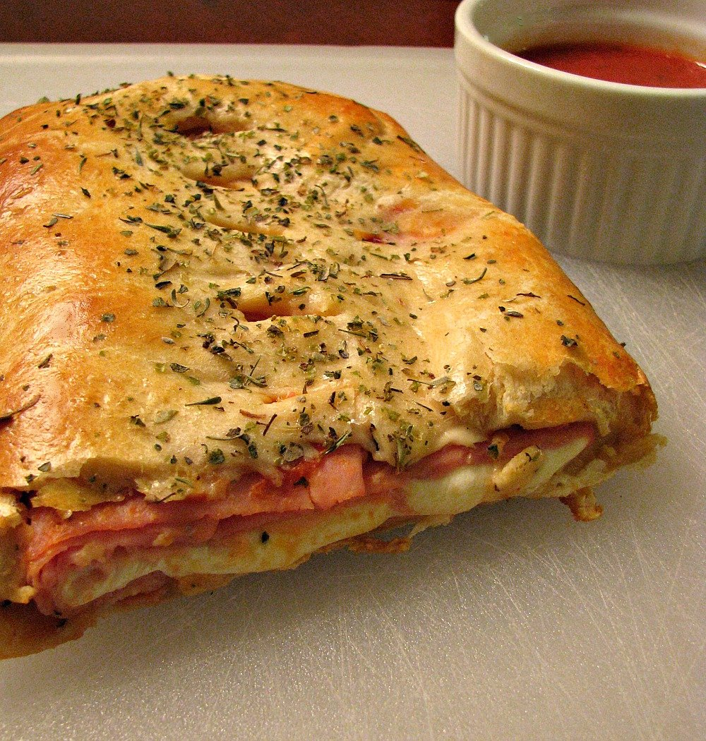 Photo of sliced Ham and Cheese Crescent Roll Stromboli on a white cutting board next to a white bowl of marinara sauce