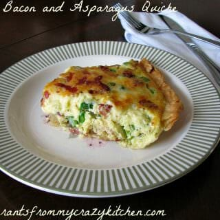 Photo of plated Asparagus and Bacon Quiche on a white plate with green trim next to silverware on a white napkin