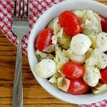 Photo of a white bowl on top of a checkered red napkin filled with Mozzarella Tomato Artichoke Salad