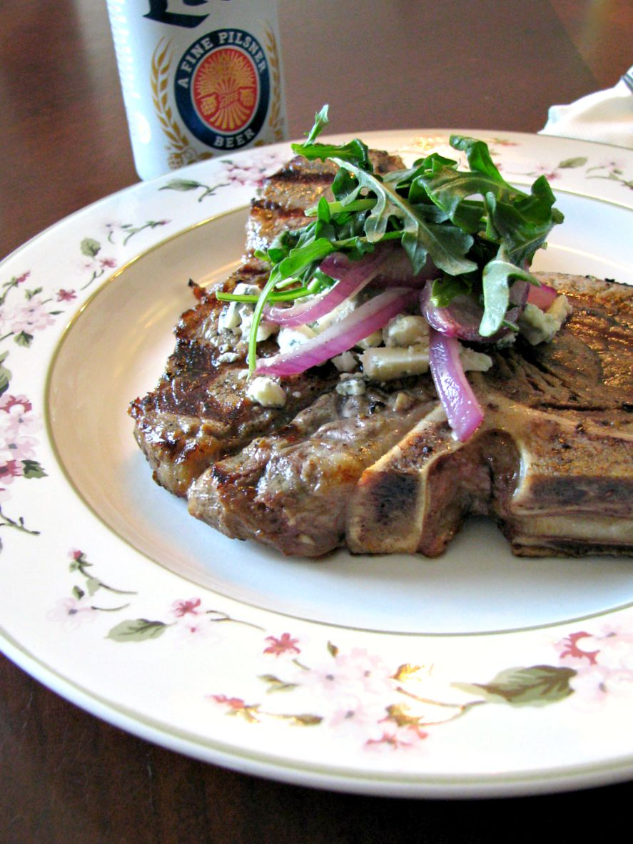 photo of a plate with beer marinated grilled porterhouse steak topped with arugula and blue cheese next to a can of beer.