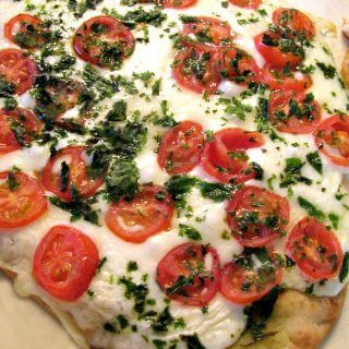 Photo of Margherita Naan Pizza on a light colored baking sheet.