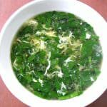 Overhead photo of Spinach Egg Drop Soup in a white bowl on a wood table