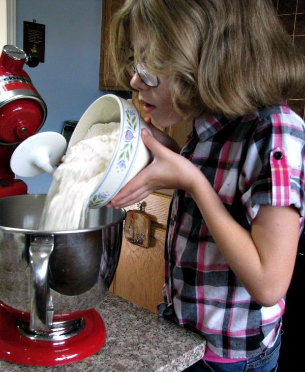 Pouring flour into mixing bowl.