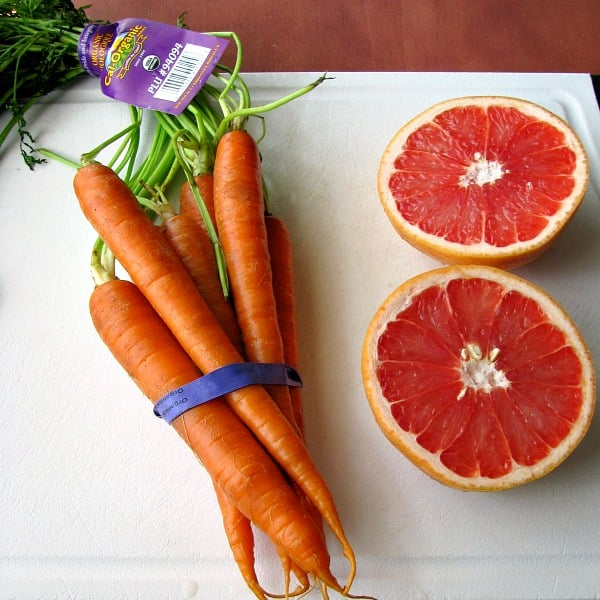 Photo of Cal-Organic Carrots wrapped together with a blue rubber band next to cut open red grapefruit on a white cutting board