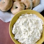 Photo of Easy Everything Bagel Dip a white creamy dip in a yellow bowl next to a basket of bagels on a brown table
