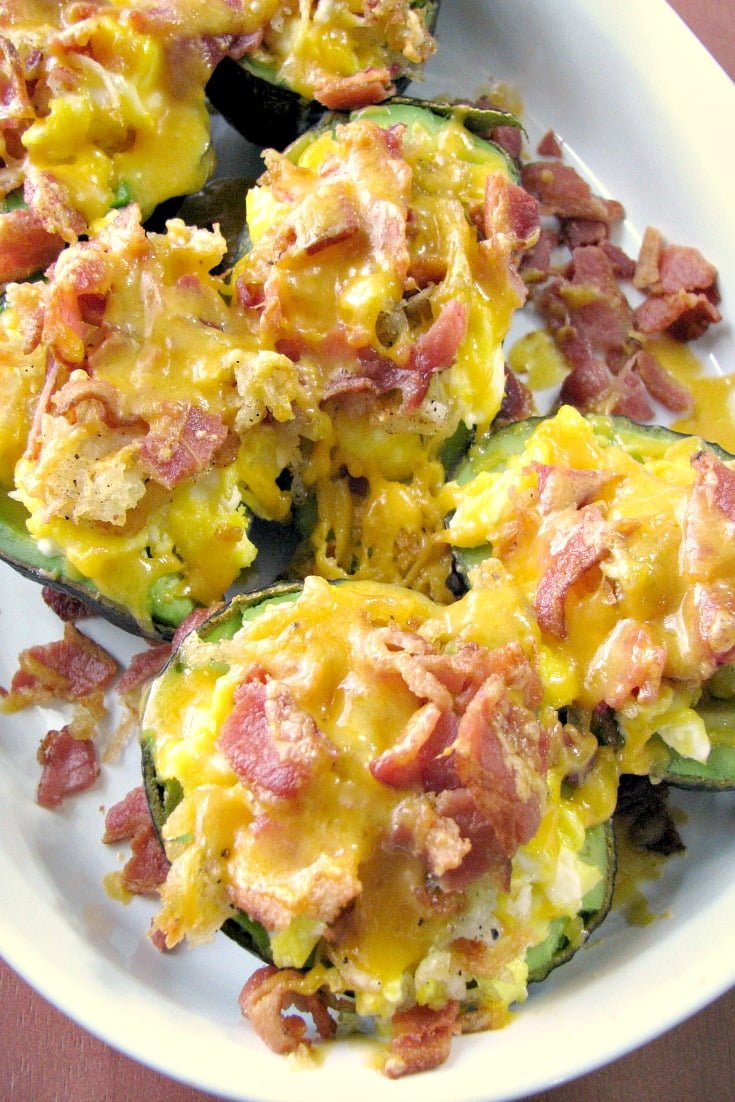 Close-up photo of baked avocados stuffed with eggs, potatoes, bacon and cheese in a white baking dish