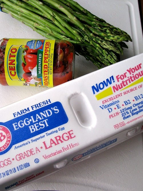 Photo of a jar of Cento brand roasted red peppers, a bunch of asparagus, and a carton of Eggland's Best Eggs