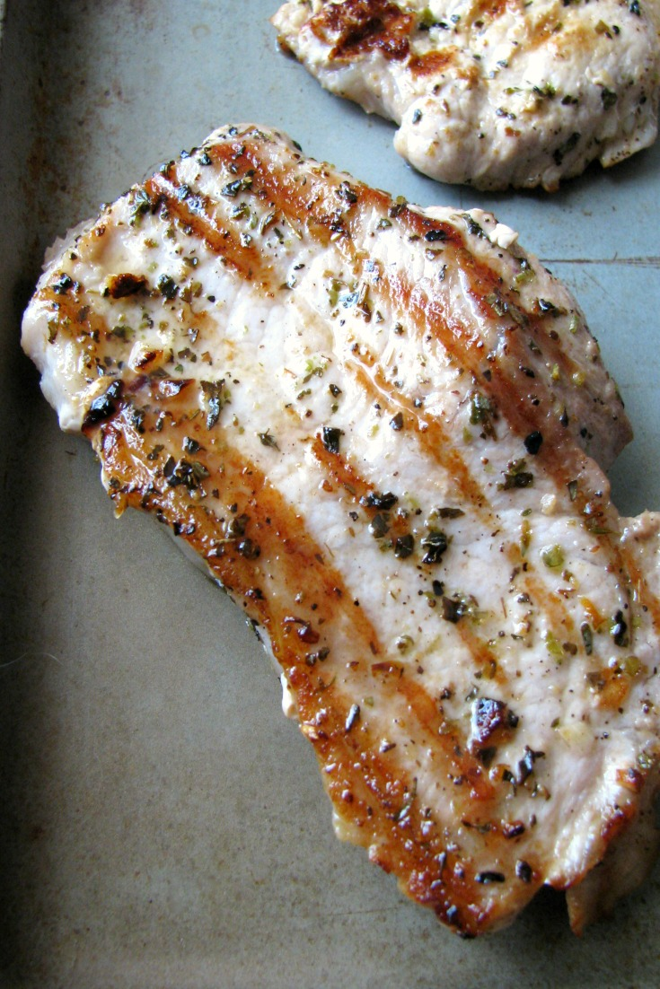 Close-up photo of one Garlic Herb Grilled Pork Chop on a silver baking pan