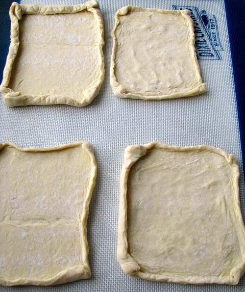 Photo of unbaked puff pastry squares on a baking pan liner.