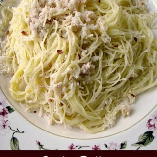 Photo of Garlic Butter Crab Pasta on a white plate with the title written at the bottom