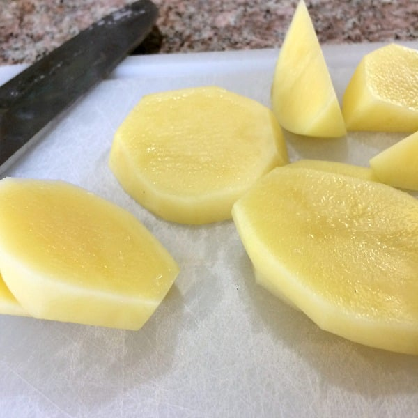 Photo of sliced peeled potatoes on a white cutting board next to a knife