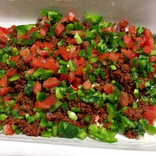 Photo of chorizo topped with tomatoes, peppers, and cilantro