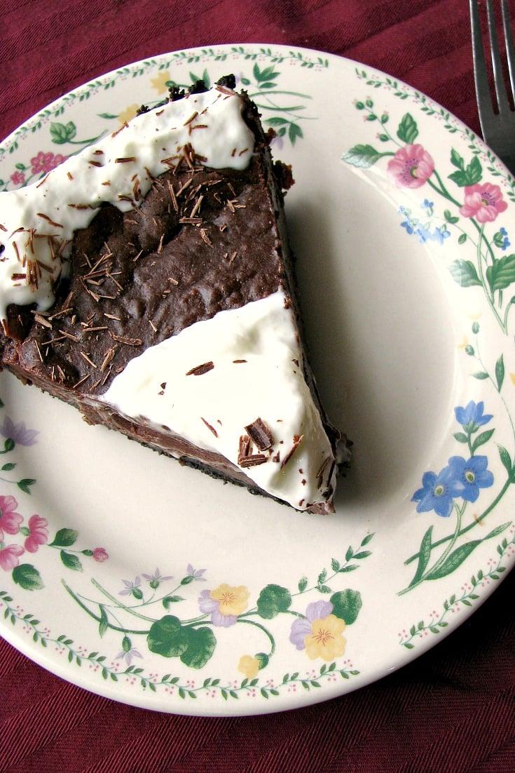 Photo of a slice of Chocolate Hazelnut Truffle Tart on a white plate with flowered trim
