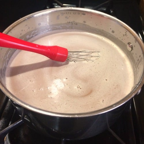Photo showing melting chocolate in a saucepan with a red handled whisk