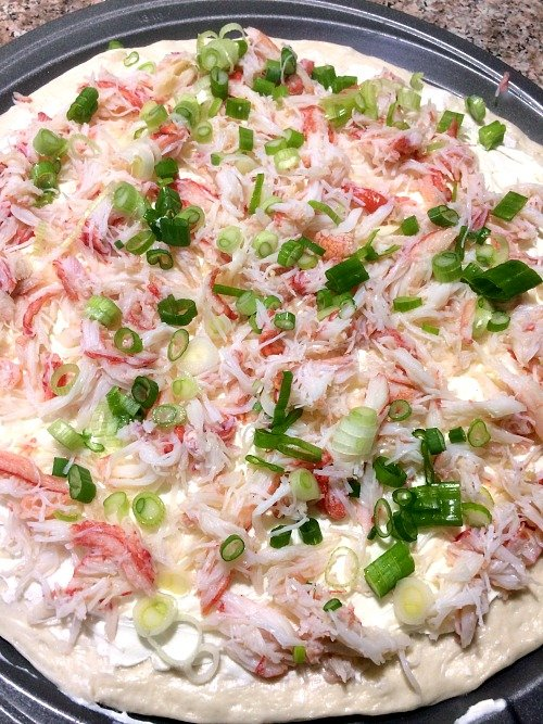 Photo of crab and scallion topped pizza dough