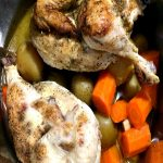 Photo of a split chicken over baby potatoes and chopped carrots with garlic in an instant pot