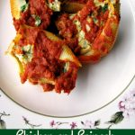 Photo of four Chicken and Spinach Stuffed Shells on a white plate with flower trim