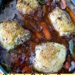 Photo of cooked chicken in red wine sauce showing four chicken thighs in a deep aluminum pan