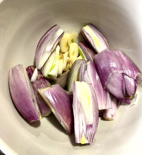 photo of sliced shallots and garlic in a white bowl