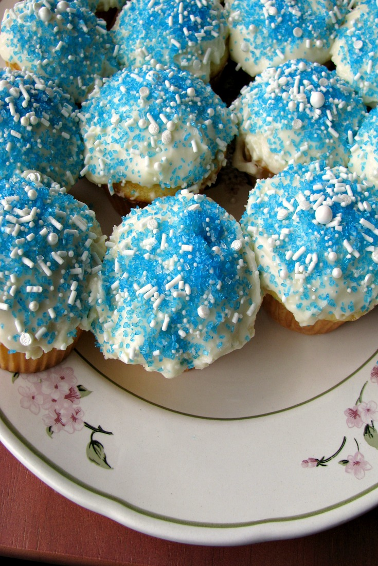 Overhead photo of Easy Champagne Cupcakes topped with champagne cream cheese frosting and blue and white sprinkles