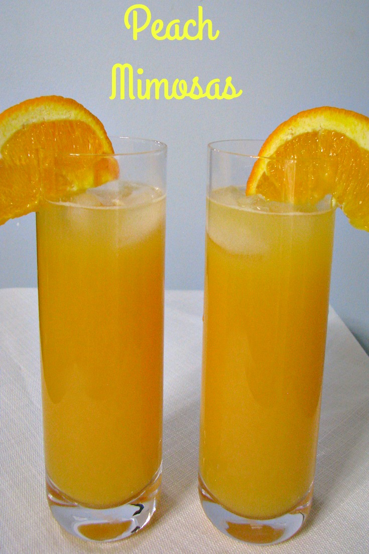 Front facing photo of two glasses of peach mimosas with orange slices on the rims