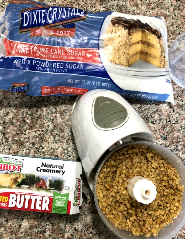 Photo of ingredients for Walnut Crumb Cookies including ground walnuts in a mini food processor butter and a package of powdered sugar