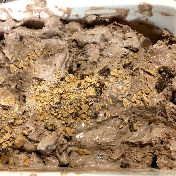 photo of semi-frozen ice cream with chopped chocolate peanut butter cups being added