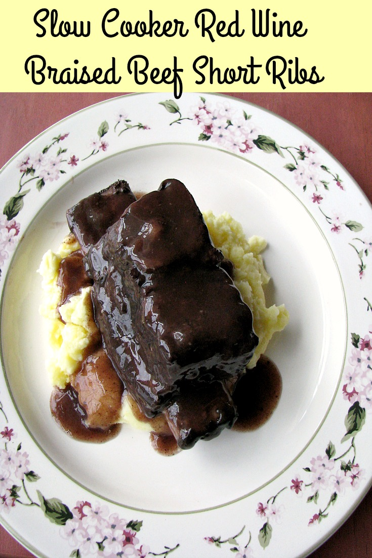 photo of slow cooker red wine braised short ribs over mashed potatoes on a white flower plate