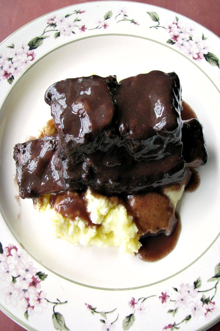 photo of plated Slow Cooker Red Wine Braised Short Ribs over mashed potatoes on a white flower trimmed plate