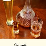 photo of a shot glass of Krupnik (honey spiced liqueur) in a shot glass next to a glass of beer a bottle and a glass on a wood table