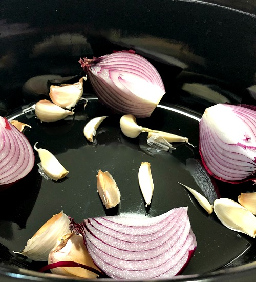 photo of quarters onions and garlic cloves in a black slow cooker insert